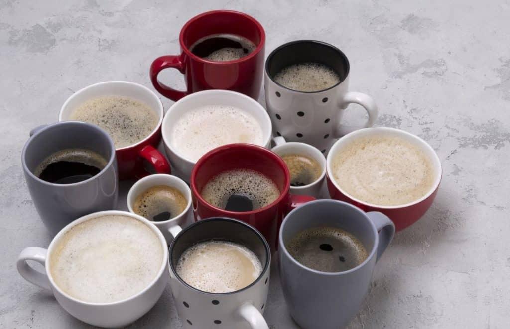 Mehrere Tassen in verschiedenen Formen, Farben und Größen stehen zusammen und sind mit unterschiedlichen Kaffeegetränken gefüllt.