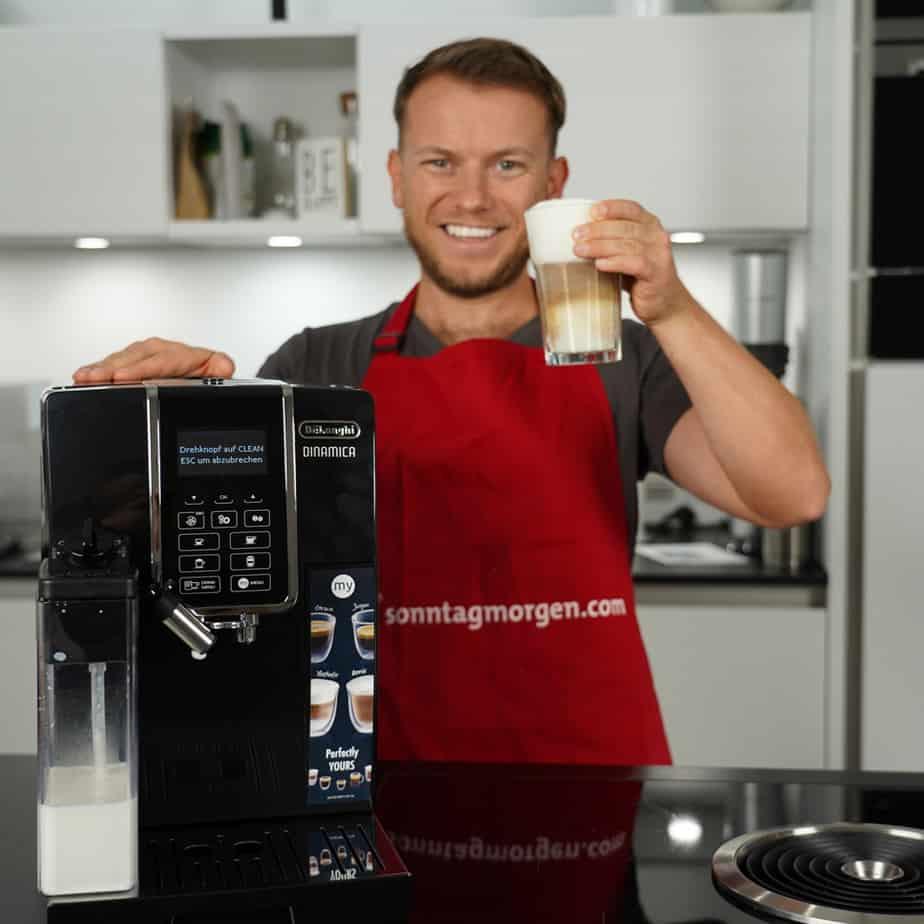 Arne von Sonntagmorgen steht hinter dem DeLonghi ECAM 350.55.B und hält ein Glas mit Latte Macchiato in der linken Hand