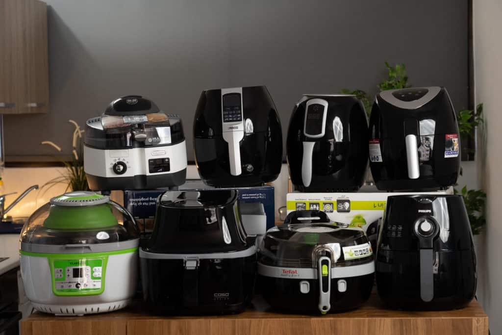 Gruppenbild mit den getesteten Heißluftfritteusen, acht von zehn Geräten (es fehlen die Gourmetmaxx Heißluftfritteuse und Tefal ActiFry Genius XL)