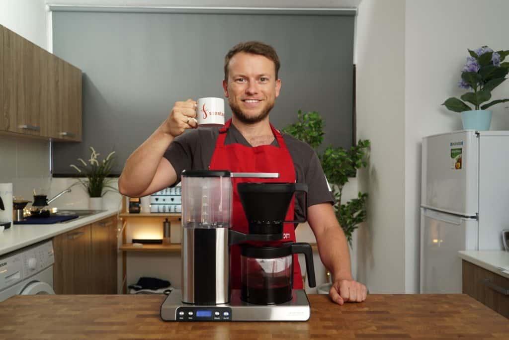 Barista Arne steht hinter der Gastroback Design Brew Advanced Kaffeemaschine mit einer Tasse in der rechten Hand