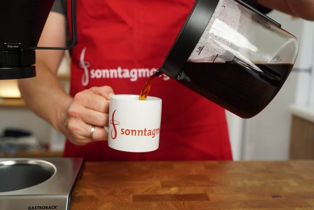 Kaffee wird aus der Kanne der Gastroback Design Brew Advanced Kaffeemaschine in eine Tasse mit Sonntagmorgen-Schriftzug gegossen