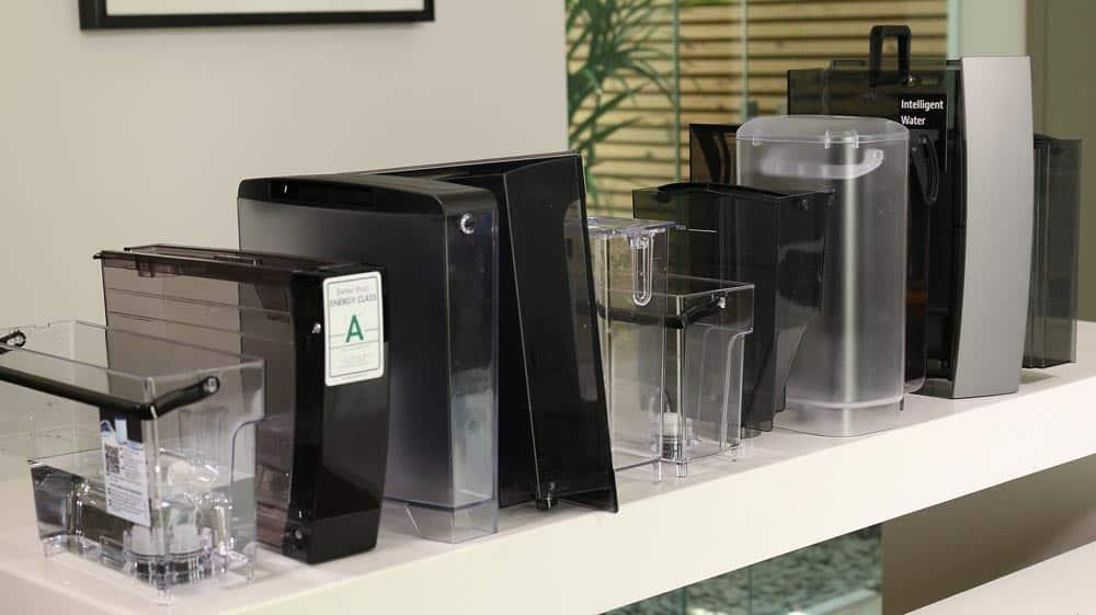 Bild zeigt eine Reihe von verschiedenen Kaffeevollautomaten-Wassertanks, die nebeneinander aufgestellt sind