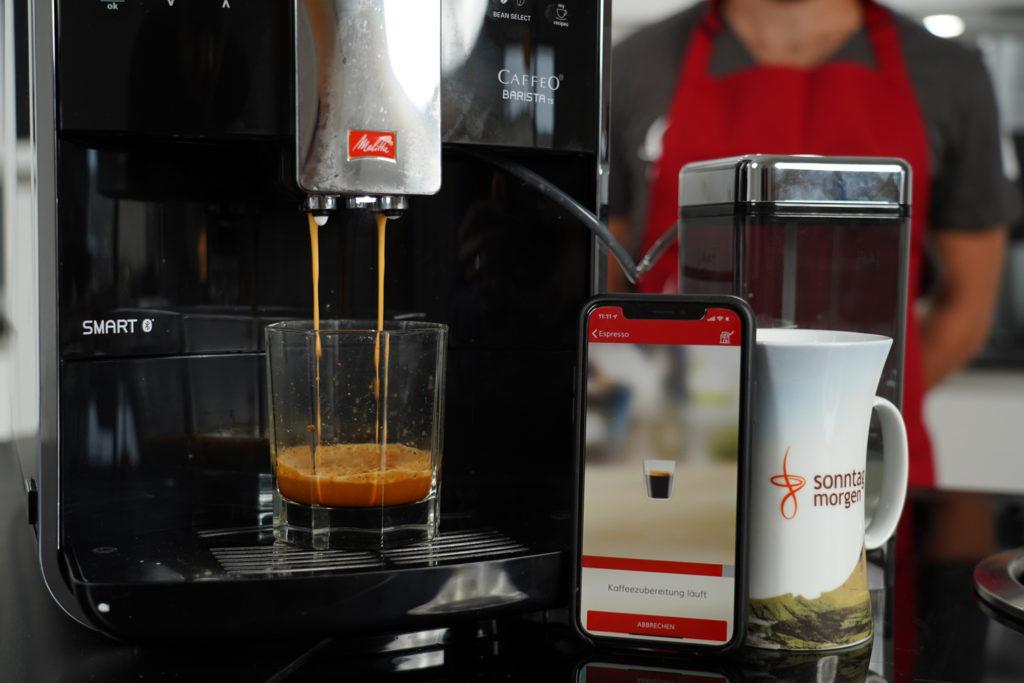 Melitta Caffeo Barista TS Smart - Espressobezug, rechts daneben ein Android Smartphone mit der Melitta-App, die den Verlauf anzeigt