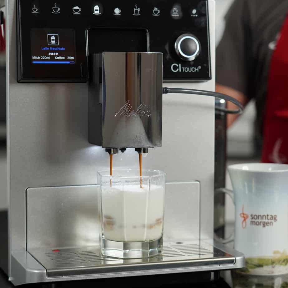 Melitta CI Touch - Espresso fließt in Glas mit geschäumter Milch