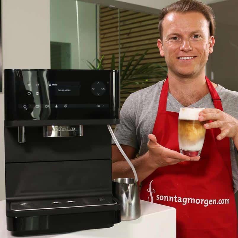 Miele CM 6350 - Arne von Sonntagmorgen.com hält einen fertig zubereiteten Latte Macchiato in der Hand, mit dem Miele CM 6350 links neben ihm