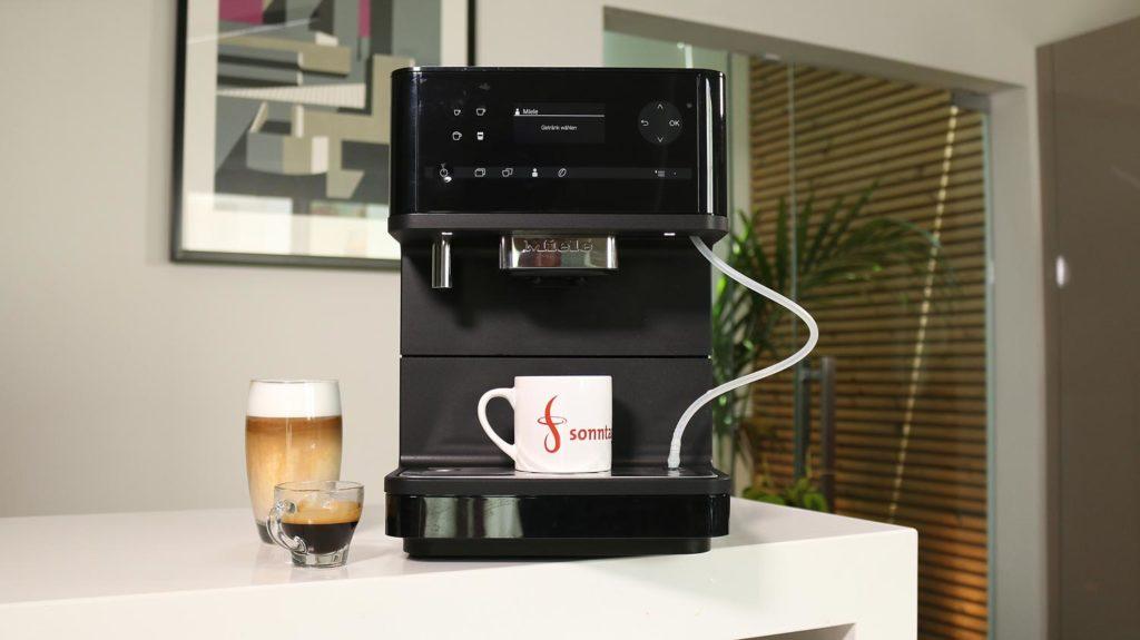 Miele CM 6350 - Gesamtansicht des Kaffeevollautomaten mit einem Latte Macchiato und Espresso links daneben