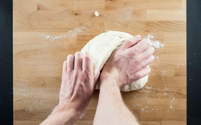 Pizzateig auf Oberfläche kneten