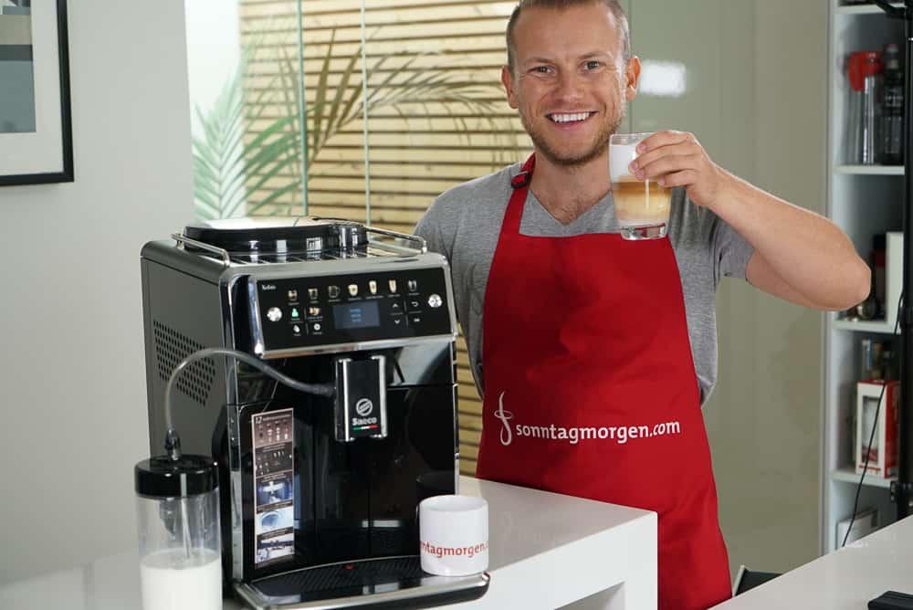 Arne von Sonntagmorgen präsentiert den Saeco Xelsis Kaffeevollautomaten mit einem fertig zubereiteten Latte Macchiato