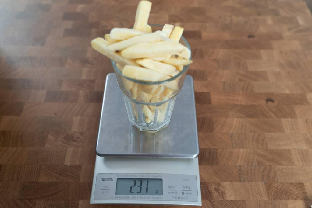 Pommes Frites werden in einem Glas auf einer Digitalwaage abgewogen